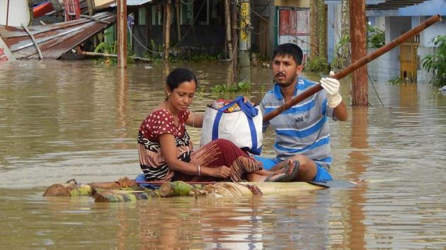 People sit on a makeshift raft after a heavy downpour at Kailashahar in Tripura. More than 70,000 people have been displaced from their homes due to last week's incessant rains.(AFP)