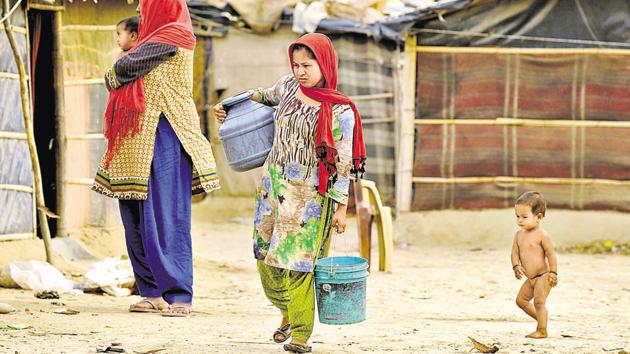 Rohingya woman walk to their tents after fetching drinking water at Chandeni Rohingya camp in Haryana's Nuh District, in Gurugram.(Parveen Kumar/HT File Photo)