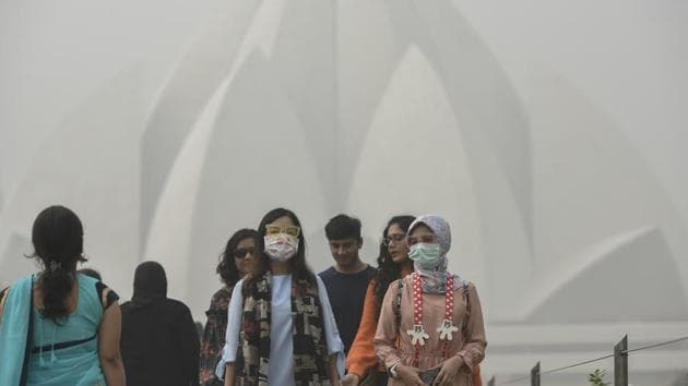 Foreign tourists wearing masks as they visit Lotus Temple on a smoggy morning in New Delhi on November 7, 2017.(Burhaan Kinu/HT File Photo)