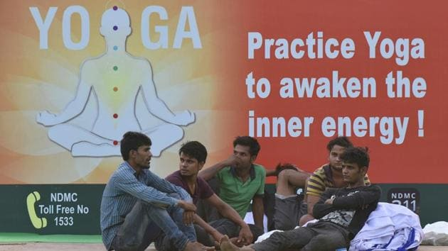 Labourers seen sitting at the lawns of Rajpath ahead of International Yoga Day, in New Delhi on June 20.(Vipin Kumar/HT PHOTO)