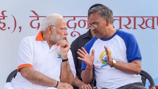 PM Narendra Modi and CM Trivendra Singh Rawat discuss a point at FRI ground in Dehradun on Thursday.(PTI)