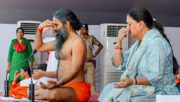 Yoga guru Ramdev Baba and Rajasthan chief minister Vasundhara Raje perform yoga during an event to set the Guinness World Record for 'The Largest Yoga Lesson' during the International Day of Yoga, in Kota on June 21, 2018.(PTI)