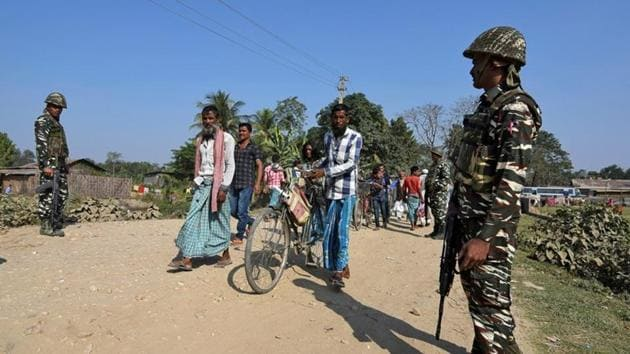 Villagers walk past Central Reserve Police Force personnel patrolling a road ahead of the publication of the first draft of the National Register of Citizens in the Juria village of Nagaon district in Assam, in 2017.(File photo)