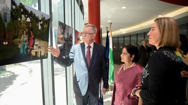 """European foreign affairs chief Federica Mogherini (R) and Minister of Foreign Affairs of India Sushma Swaraj (C) look at the """"Indian diaspora in the European Union"""" exhibition in EEAS Atrium at the EU headquarters in Brussels.(/AFP PHOTO)"""