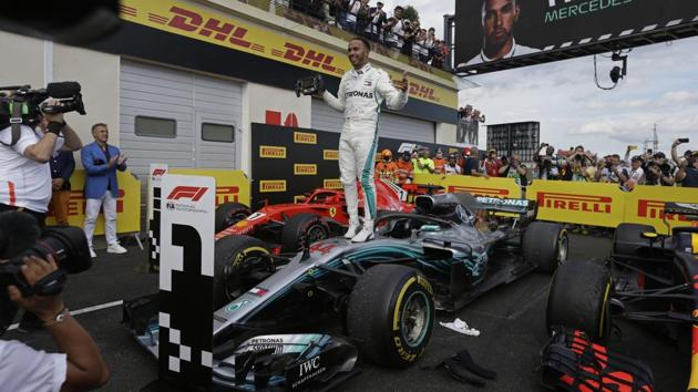 Mercedes driver Lewis Hamilton celebrates while standing on his car after winning the Formula One French Grand Prix at the Paul Ricard racetrack in Le Castellet, southern France, on Sunday.(AP)