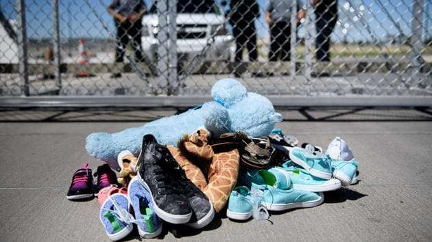 A file photo shows security personal standing before shoes and toys left at the Tornillo Port of Entry in Tornillo, Texas on June 21 where minors crossing the border without proper papers have been housed after being separated from adults(AFP File Photo)