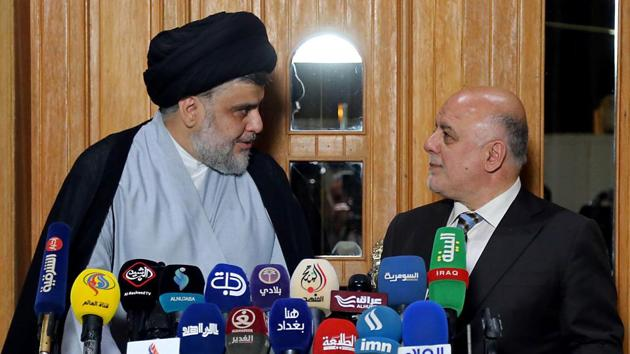 Iraqi Prime Minister Haider al-Abadi (R) attend a press conference with Iraqi Shiite cleric and leader Moqtada al-Sadr in Najaf on June 23, 2018. /(AFP)