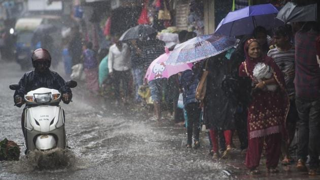 A biker drives through a waterlogged road at Dadar in Mumbai on Saturday.(Pratik Chorge/HT Photo)