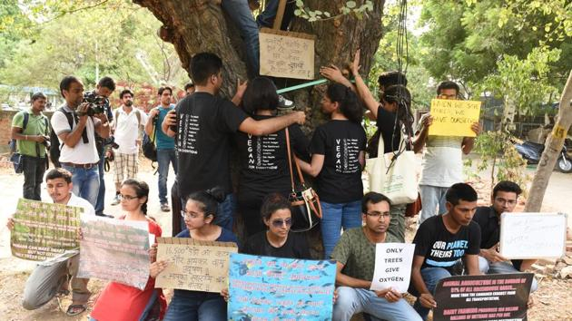 People hold placards as they protest against the cutting of trees at Sarojini Nagar in New Delhi, on Sunday.(Sonu Mehta/HT Photo)