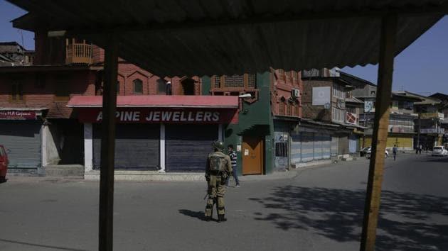 A paramilitary soldier stands guard at a closed market during a shutdown in Srinagar.(AP Photo)