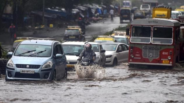 Mumbai rains: Vehicles wade through water-logged tracks during heavy rains, in Mumbai on Monday, June 25, 2018.(PTI)