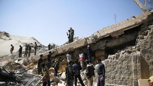 Policemen and people search for victims at the site of a Saudi-led airstrike on the police headquarters in Sanaa, Yemen. File Photo(AP)