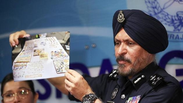 Malaysia's commercial crime investigations chief Amar Singh shows a picture of jewellry seized from properties linked to former prime minister Najib Razak in Kuala Lumpur on Wednesday.(Vincent Thian/AP)