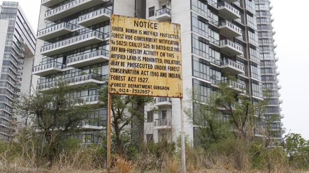 A signboard, metres away from a new building erected on bed of Ghata lake, warns that non-forest activities on the land are liable to action under Forest Act.(Yogendra Kumar/HT PHOTO)