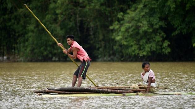 Villagers use a makeshift raft to cross a flooded area in the Nagaon district in Assam.(REUTERS)