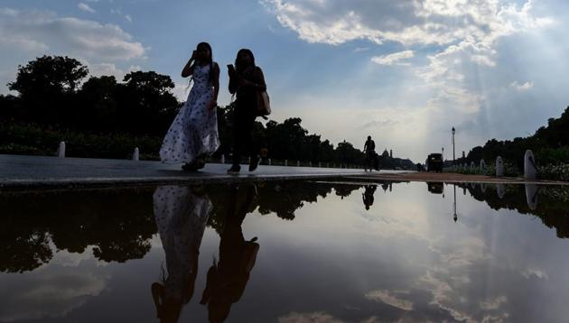 Women walk past a puddle of water at Rajpath after a short spell of rain in New Delhi on Thursday. Pre-monsoon showers hit the capital this week, with light rain on Monday and Tuesday and heavier showers on Wednesday.(PTI)