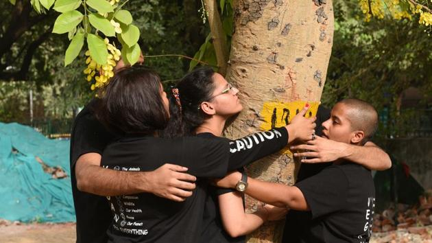 People hug a tree as they protest against the cutting of trees at Sarojini Nagar in New Delhi, India, on Sunday, June 24, 2018.(Sonu Mehta/HT PHOTO)