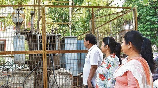 Sushant Lok residents seen standing near a power transformer. They had to spend night without electricity as power cuts emerge as big menace with soaring humidity and increasing consumption demand, in Gurugram on Thursday