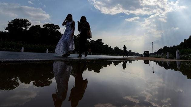 Women walk past a puddle of water at Rajpath after a short spell of rain in New Delhi on Thursday.(PTI Photo)