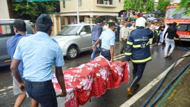 Indian Air Force personnel and a Mumbai Fire personnel carry the body of one of the victims from the site of the chartered plane crash, in Ghatkopar in Mumbai.(PTI Photo)