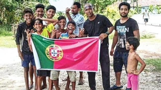 Youths of Mirpur, a village in West Bengal, with the flag of Portugal. They are gunning for Cristiano Ronaldo at the FIFA World Cup.(HT Photo)
