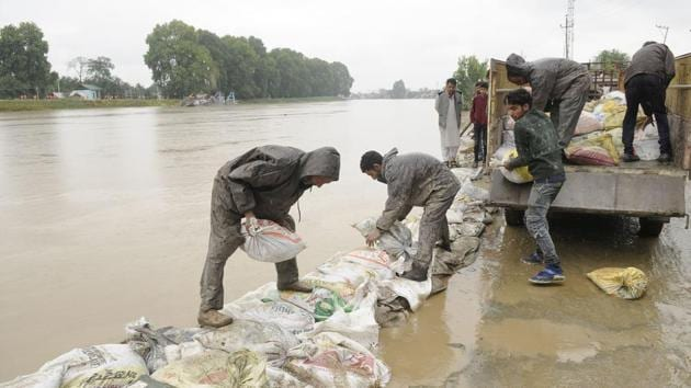 Labourers place sandbags along the Jhelum river bank in an attempt to prevent flood water from spilling into residential areas in Srinagar on Saturday.(Waseem Andrabi / HT Photo)