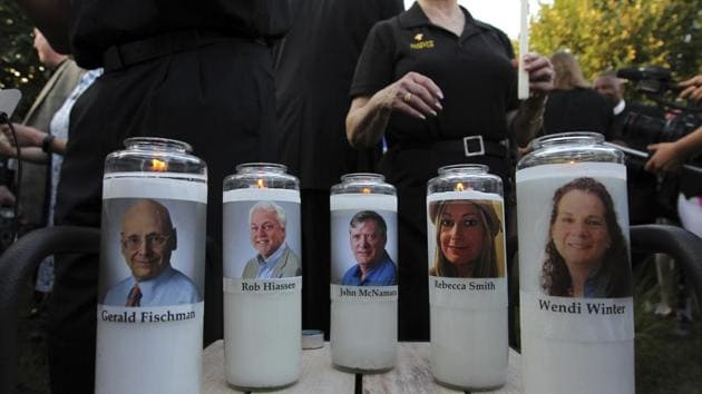 Photos of five journalists adorn candles during a vigil across the street from where they were slain in their newsroom in Annapolis, United States.(AP)