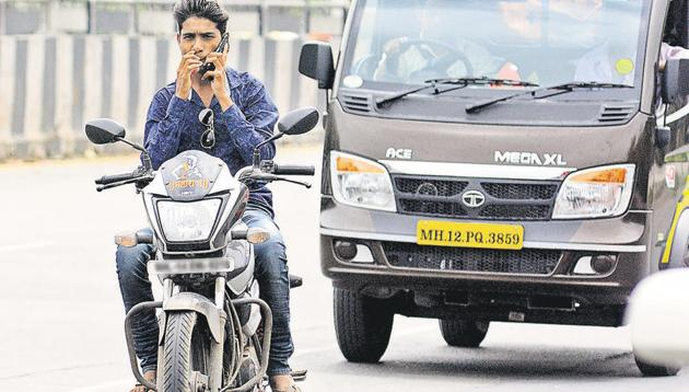A motorist speaks on a mobile phone while riding a bike at Ahmednagar road on Monday.(SHANKAR NARAYAN/ HT PHOTO)