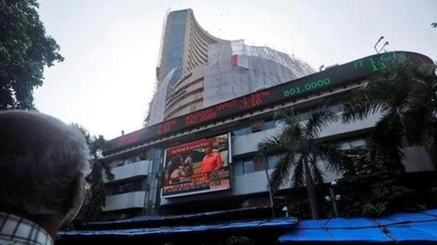 People watch a large screen displaying India's benchmark share index on the facade of the Bombay Stock Exchange (BSE) building in Mumbai.(Reuters File Photo)