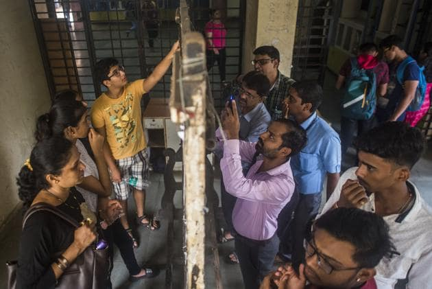 Students and parents check the first merit list of FYJC at Ruia College, Matunga on Thursday.(Pratik Chorge/HT Photo)