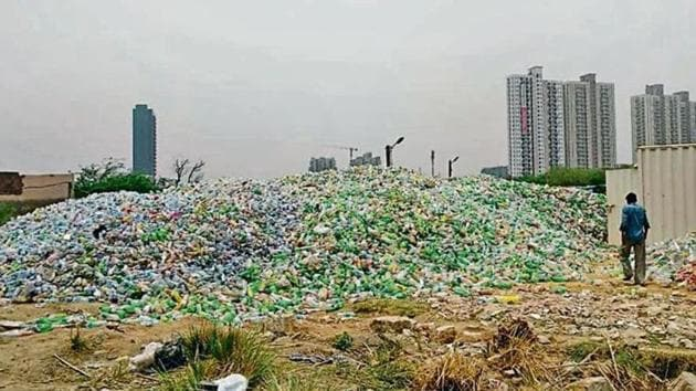 Waste plastic bottles dumped in Basai came to light in June after a black-necked stork was spotted with a plastic bottle cap around its beak.(Pankaj Gupta/ HT Photo)