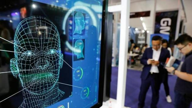 Visitors check their phones behind the screen advertising facial recognition software during Global Mobile Internet Conference (GMIC) at the National Convention in Beijing, China.(REUTERS/Damir Sagolj/Files)