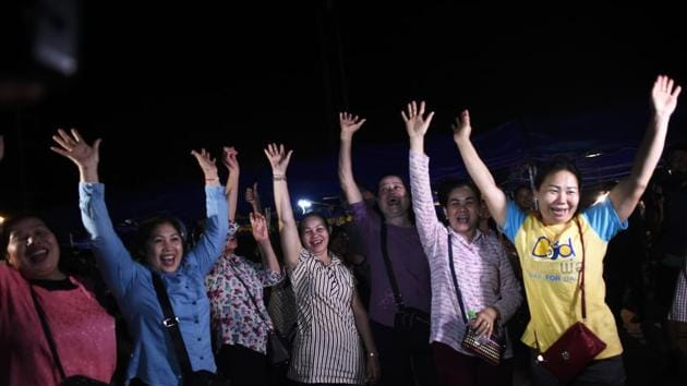 Volunteers celebrate at a makeshift press centre in Mae Sai district of Chiang Rai province on Tuesday after the twelve boys and their football coach were rescued.(AFP Photo)