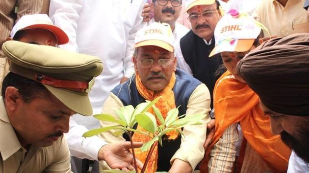 Chief minister Trivendra Singh Rawat plants a sapling to save Kosi river on Monday.(HT Photo)