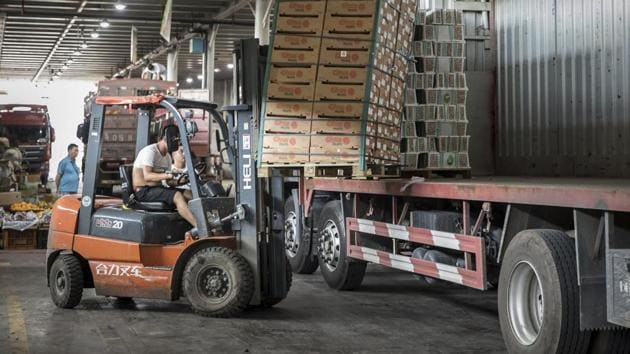 A man uses a forklift to unload a pallet of imported fruit from a truck at a wholesale market in Shanghai. China released its gross domestic product figures on July 16.(Bloomberg)