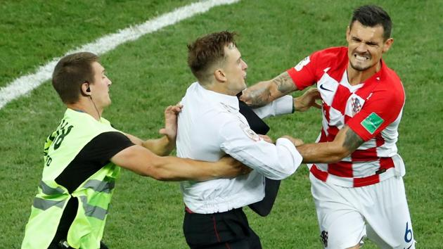 A steward apprehends a pitch invader as he approaches Croatia's Dejan Lovren during the FIFA World Cup 2018 final.(REUTERS)