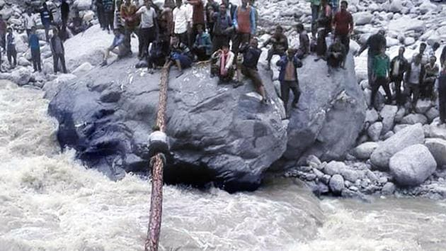 A villager crosses the river by crawling over a tree trunk as others hold it in place.(HT Photo)