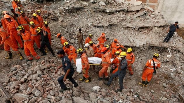 <p>Rescue workers carry out the body of a victim at the site of a collapsed residential building at Shahberi village in Greater Noida, a day after the collapse....