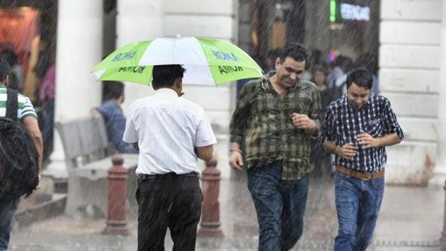 People caught up in rain in New Delhi on Monday, July 16, 2018. Today, it is considered hazardous to even stand in the rain in our noxious cities where a downpour washes the air of suspended pollutants.(Sushil Kumar/HT PHOTO)