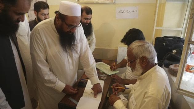 Hafiz Saeed, center, head of the Pakistani religious party Jamaat-ud-Dawa, affixes his thumb impression before casting a vote in Lahore, Pakistan, Wednesday, July 25, 2018.(AP File Photo)