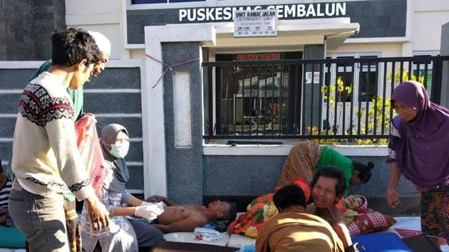 A paramedic gives treatment to injured people outside of a hospital after an earthquake hit Sembalun Selong village in Lombok Timur, Indonesia.(ANTARA FOTO/via Reuters)