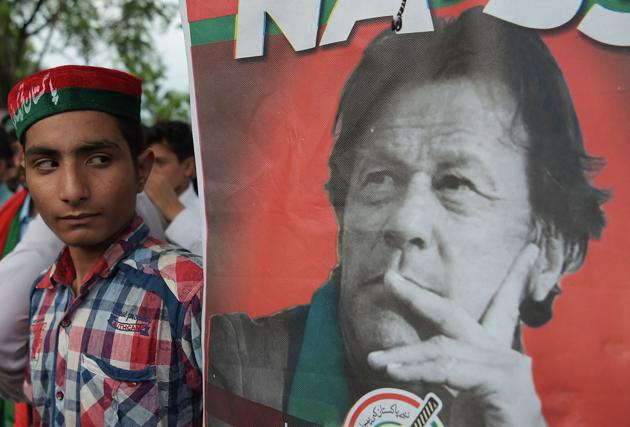 A supporters of Pakistan's cricketer-turned politician and head of the Pakistan Tehreek-e-Insaf (Movement for Justice) party Imran Khan stands next to poster with a picture of Khan as they gather near his residence in Islamabad on July 26, 2018. Today, instead of rushing to engage Imran, New Delhi should let the new leader establish his bona fides for combating terrorism.(AFP)