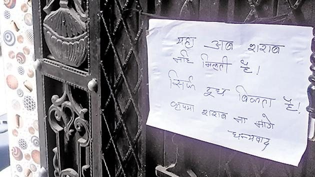 A woman who gave up bootlegging to take up dairy business pastes a notice outside her house in south Delhi's Sangam Vihar.(HT Photo)