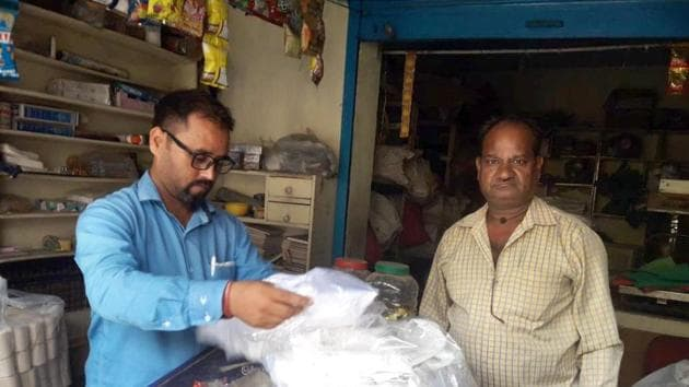 Member of anti-polythene squad issues challan to a shopkeeper for keeping polythene bags in Dehradun.(HT Photo)