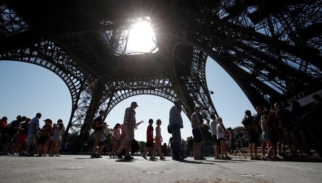People stand in line at an information booth following the closure of the Eiffel Tower as part of a strike by employees over lengthening queues during the peak summer tourist season in Paris, France, August 2, 2018.(REUTERS)