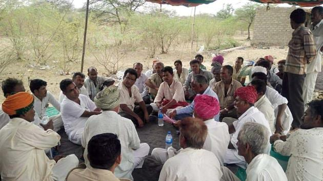 Villagers sit on a dharna outside a liquor shop at Mithdau village in Barmer.(HT Photo)