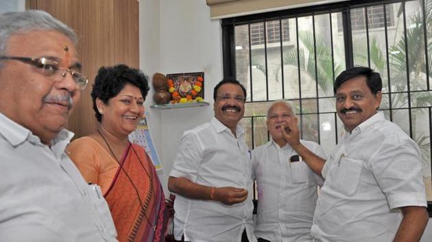 Sangli's guardian minister and cabinet minister Subhash Deshmukh feeds sweet to Sangli BJP's MLA Sudheer Gadgil in the presence of BJP leader Neeta Kelkar and BJP district president Prithviraj Desmukh.(UDAY DEOLEKAR/HT PHOTO)