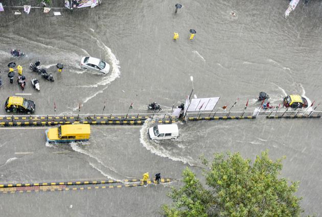 Vehicles wade through a waterlogged road at King's Circle in July.(HT Photo)