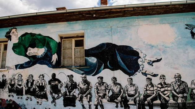 """This picture shows a reproduction of the painting """"Over the city"""" by Marc Chagall, painted on a wall of a house during an annual open-air gallery event, dedicated this year to the New York's Museum of Modern Art (MoMA), in the village of Staro Zhelezare near Plovdiv, on August 4.(AFP Photo)"""