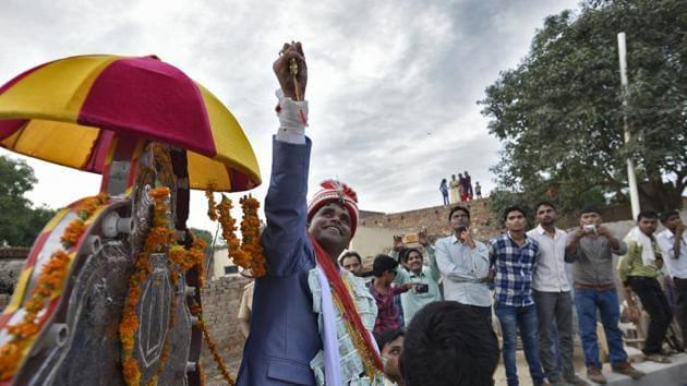 Sanjay Jatav, 27, sits on a buggy, escorted by the police as he reaches with the wedding procession (Baraat) to Nizampur, in Kasganj, Uttar Pradesh. Sanjay Jatav, took out a wedding procession in UP's Kasganj to defy caste prejudice.(Burhaan Kinu/HT PHOTO)